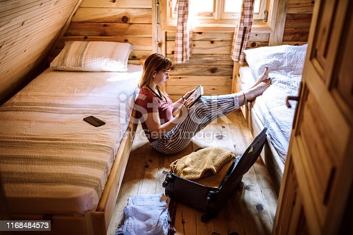 Young Woman sitting on floor in log cabin and using digital tablet, luggage is near her