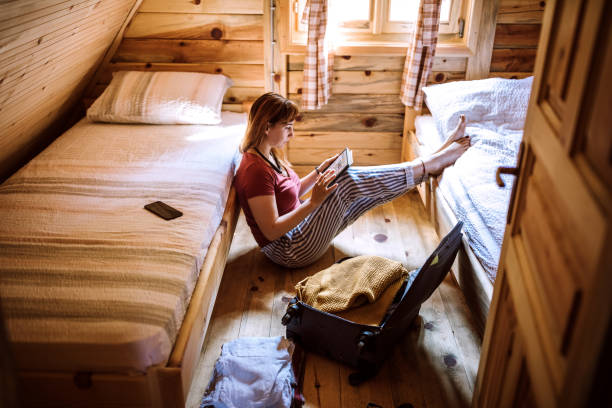 Woman sitting in log cabin and using digital tablet stock photo
