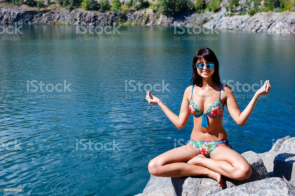 Woman sitting in lotus position on mountain river background stock photo