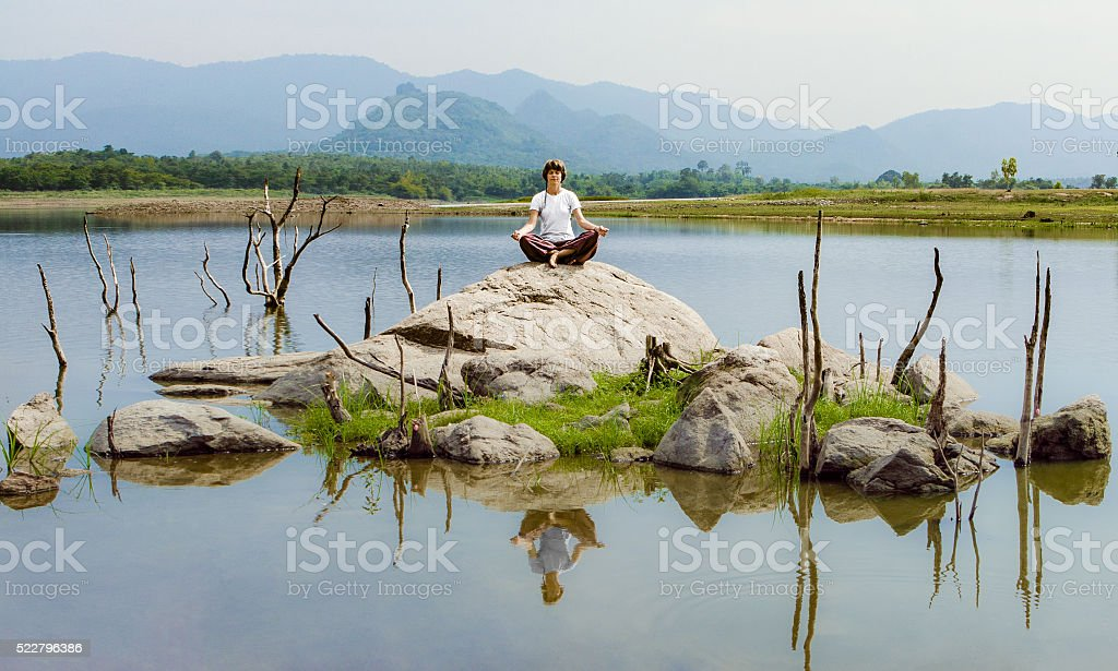 Woman sitting in lotus position on rock by the lake stock photo