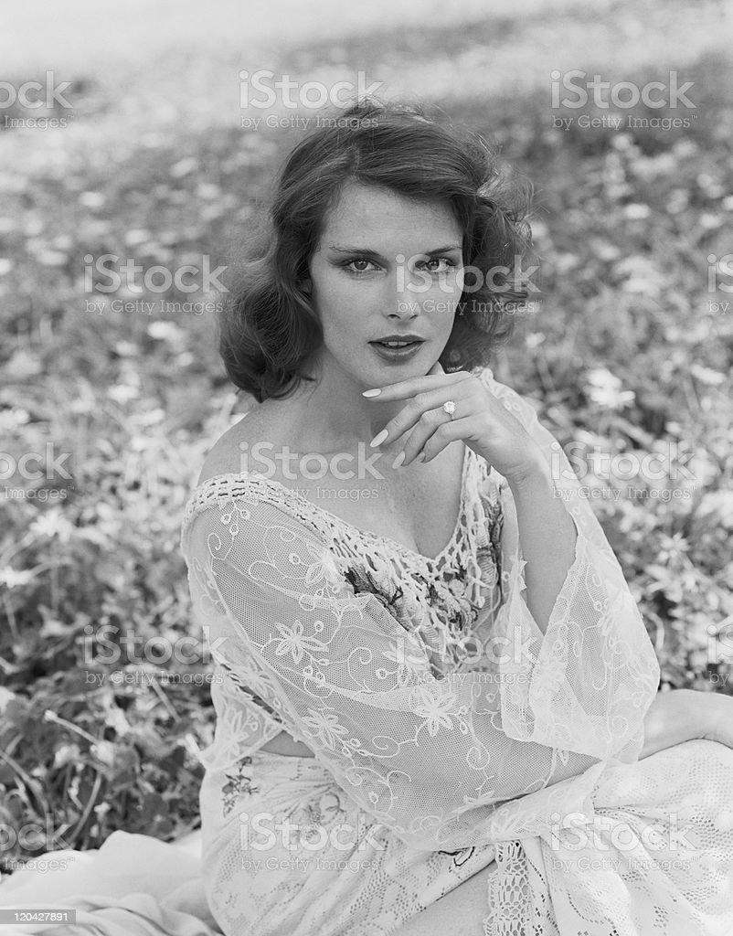 Woman sitting in meadow, portrait stock photo