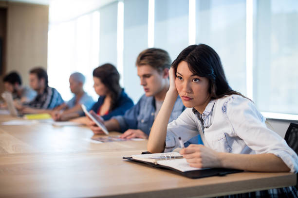 Woman sitting in meeting room with her colleagues stock photo