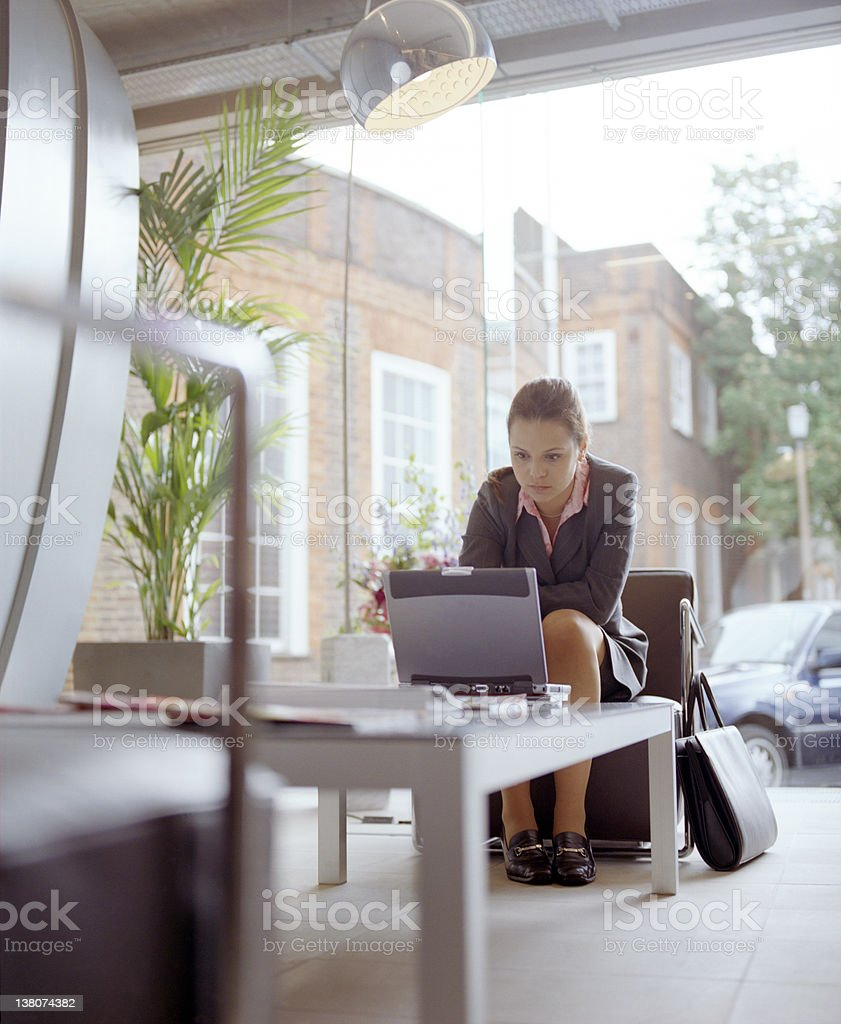Woman sitting in outdoor lounge working alone stock photo