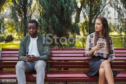 istock Woman sitting in park with man using smartphone 912931224