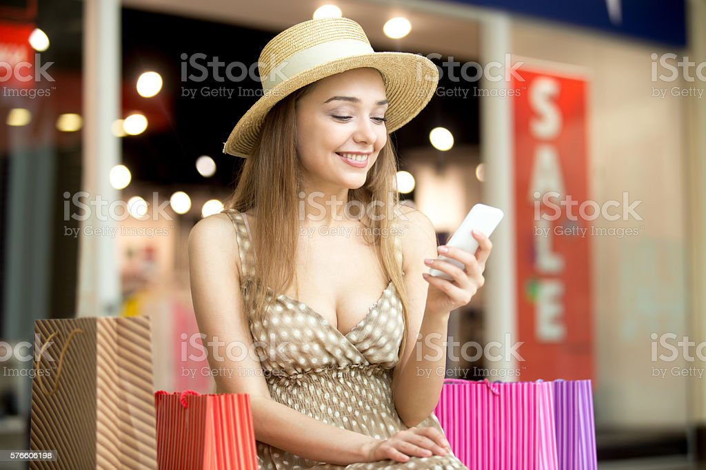 Woman sitting in shopping centre with mobile phone smiling - foto stock