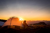 Adventurous woman watching sunset from tent in Whistler backcountry mountains.