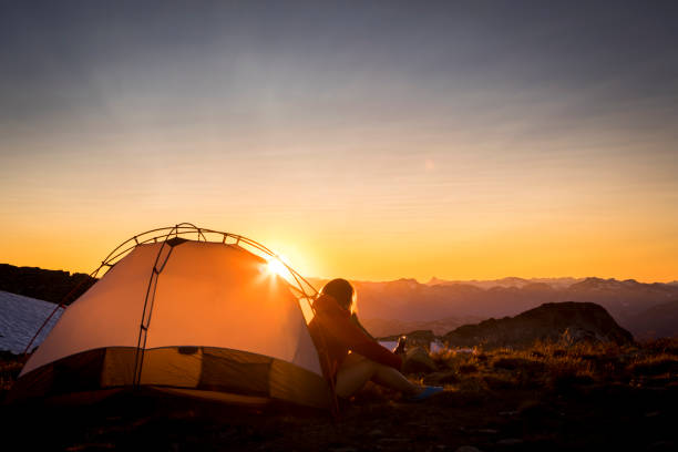 Woman sitting in tent looking at sunset. stock photo