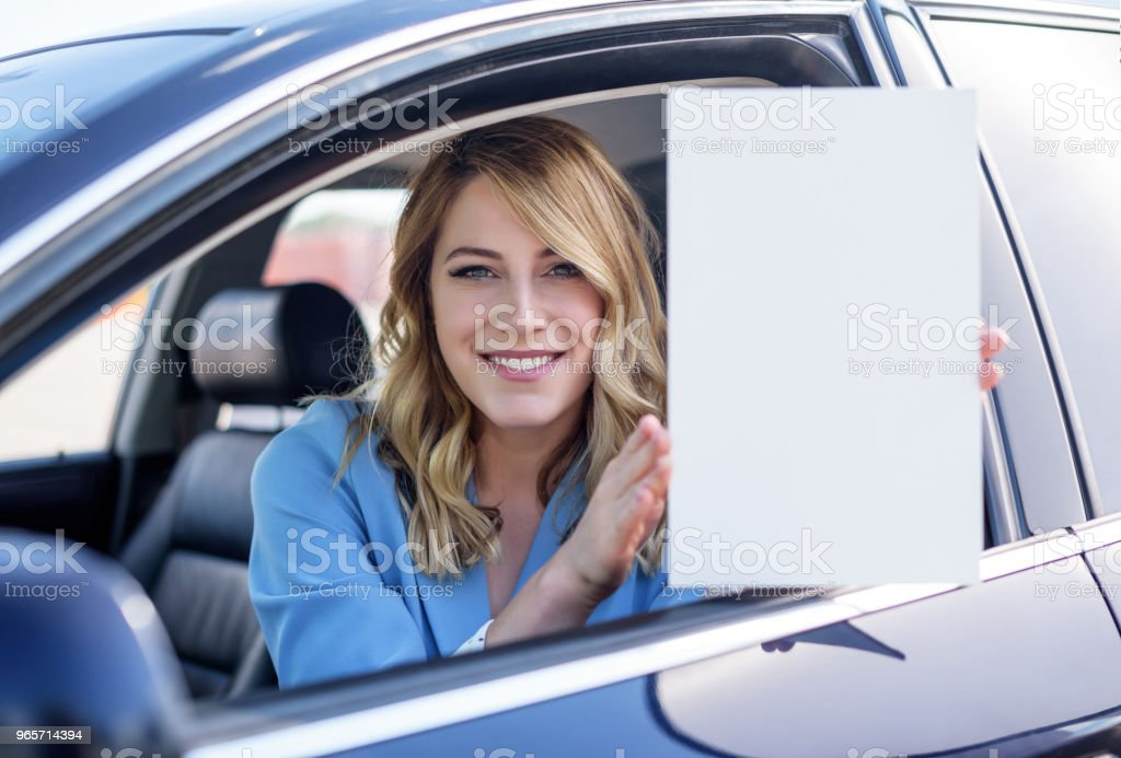 Woman sitting in the car and holding a white blank poster - Royalty-free Adult Stock Photo