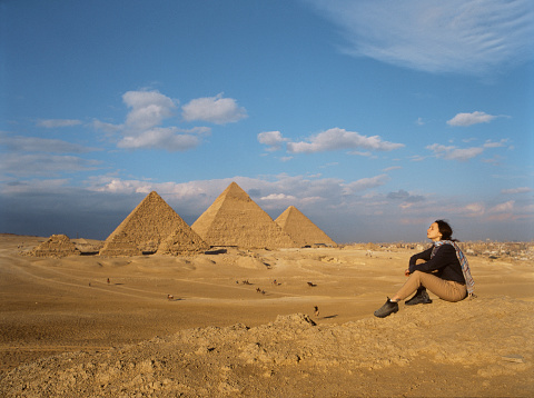 Young woman sitting in the desert near the Giza pyramids