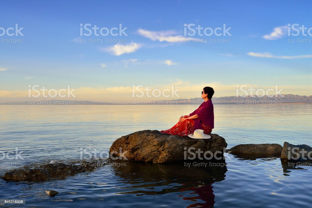 A woman sitting in the lake view stock photo