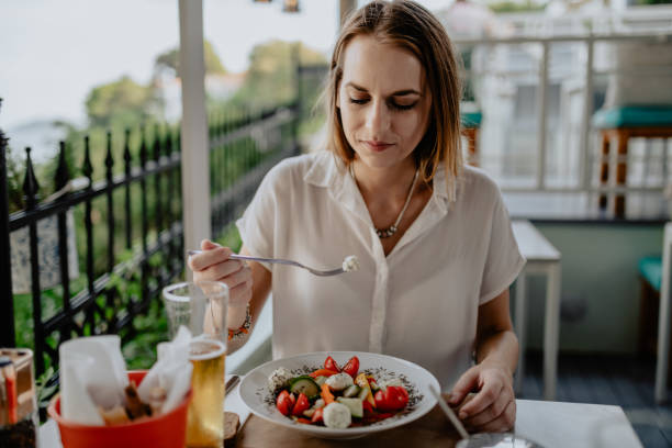 Woman sitting in the restaurant and eating salad on a sunny day stock photo