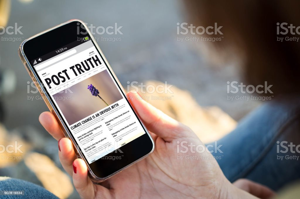 woman sitting in the street holding her smartphone reading post truth stock photo