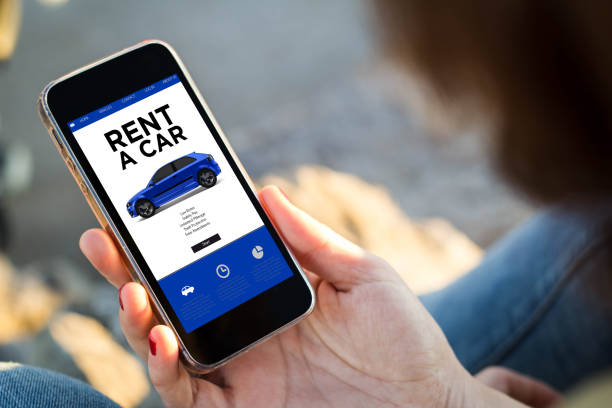 woman sitting in the street holding her smartphone rent a car stock photo