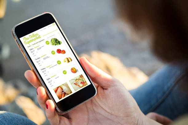 woman sitting in the street shopping groceries with her smartphone stock photo