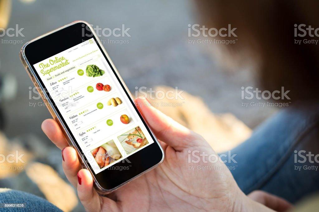 Frau sitzt auf der Straße einkaufen Lebensmittel mit ihrem smartphone – Foto