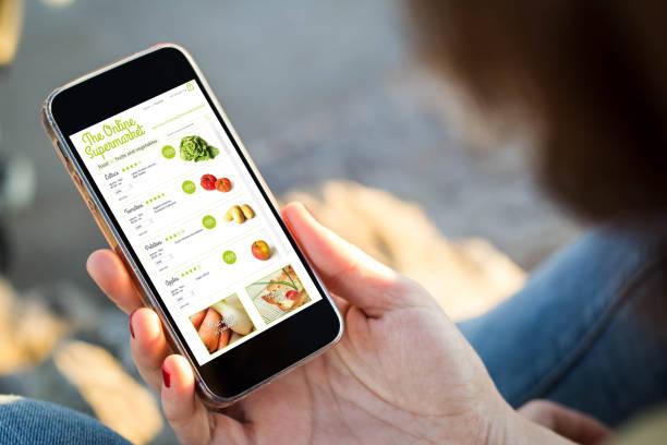 vrouw zitten in de straat winkelen boodschappen met haar smartphone - webshop stockfoto's en -beelden