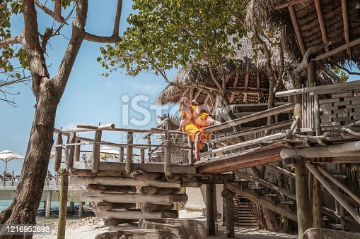 Woman sitting in rustic driftwood Treehouse designed in Balinese outdoor living Architecture on tropical Maldives Island.