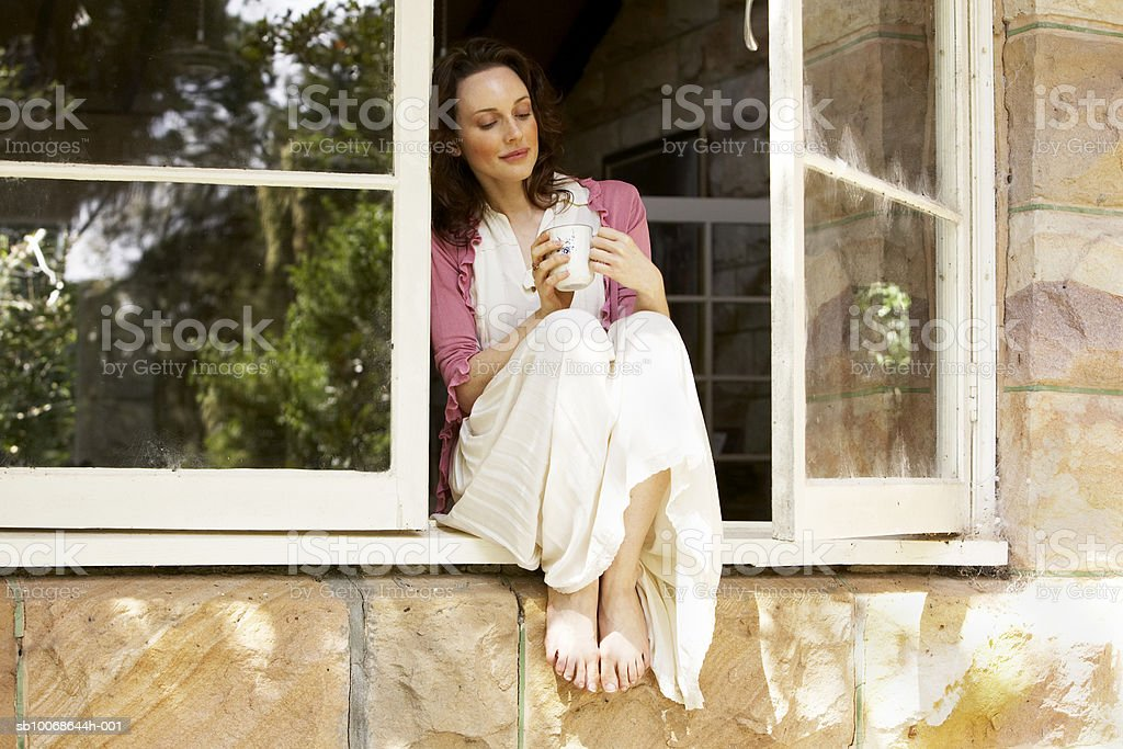 Woman sitting in window with coffee cup royalty-free stock photo