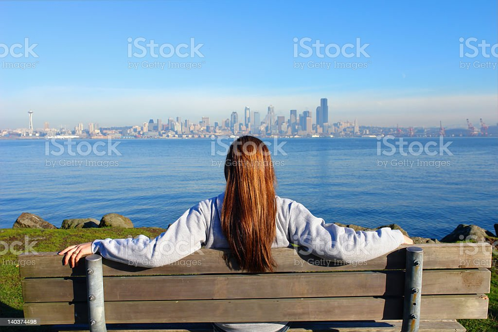 Woman sitting in wooden bench watching the city view stock photo