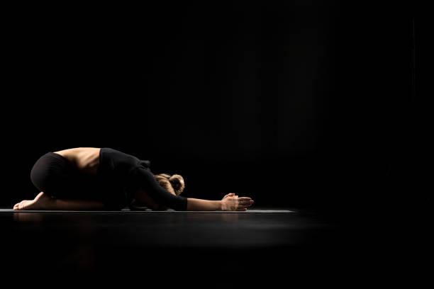 frau sitzt in yoga-position - kundalini yoga stock-fotos und bilder