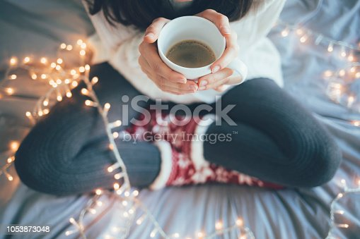 Woman sitting at home legs crossed on bed, holding a cup of coffee, christmas decoration.