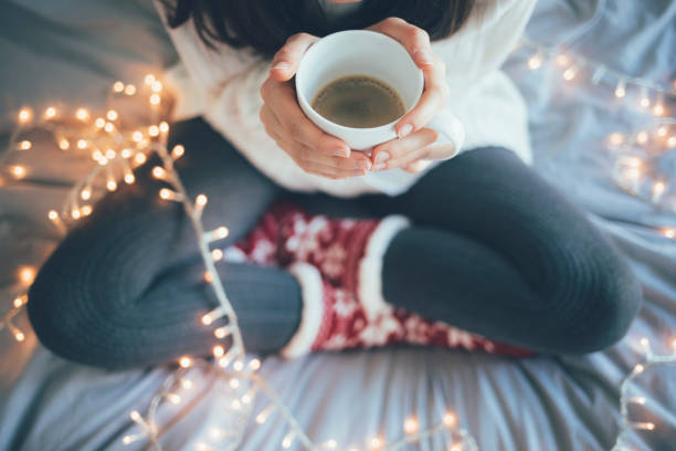 Woman sitting legs crossed on bed and holding a cup Woman sitting at home legs crossed on bed, holding a cup of coffee, christmas decoration. chalet stock pictures, royalty-free photos & images