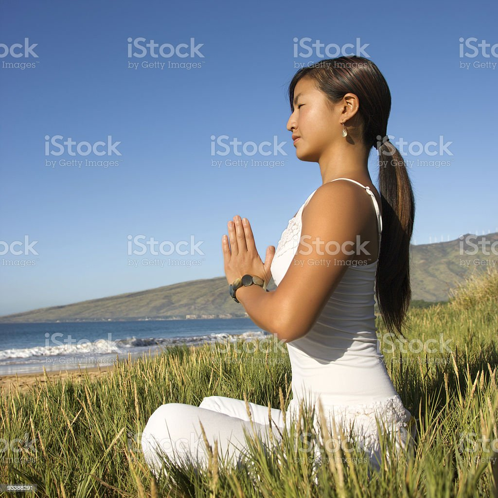 Woman sitting meditating outdoors royalty-free stock photo