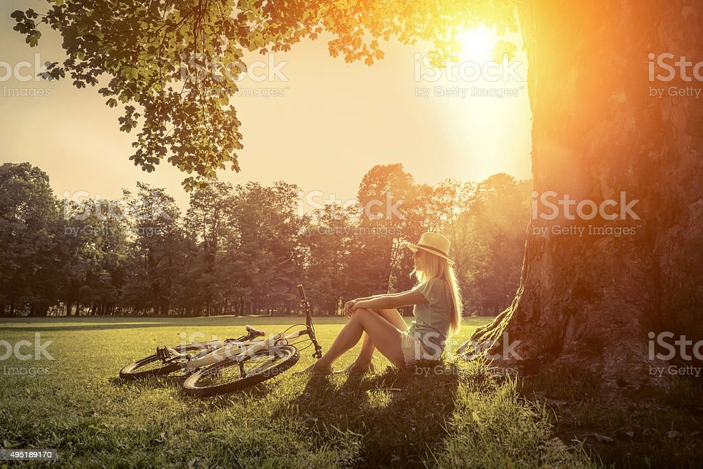 Woman sitting near her bicycle in the park under sun stock photo