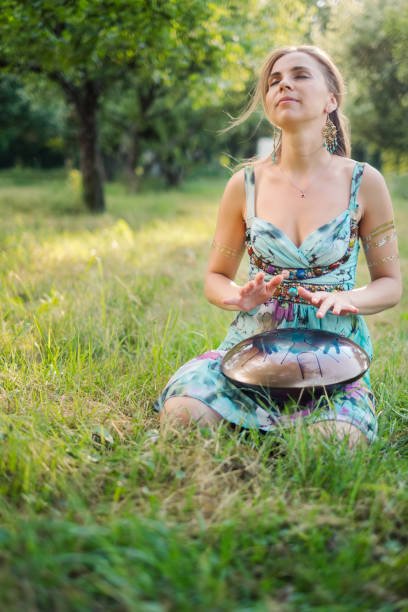 Woman sitting near in the park and playing on happy drum stock photo