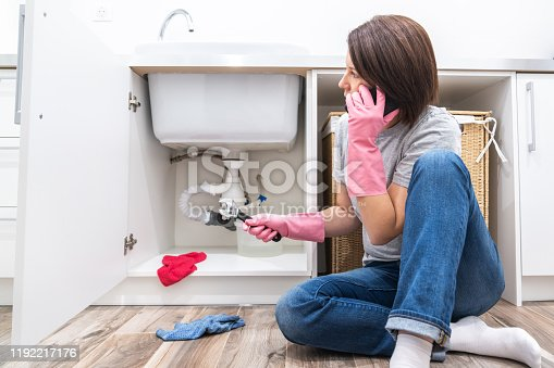 Woman sitting near leaking sink calling for help
