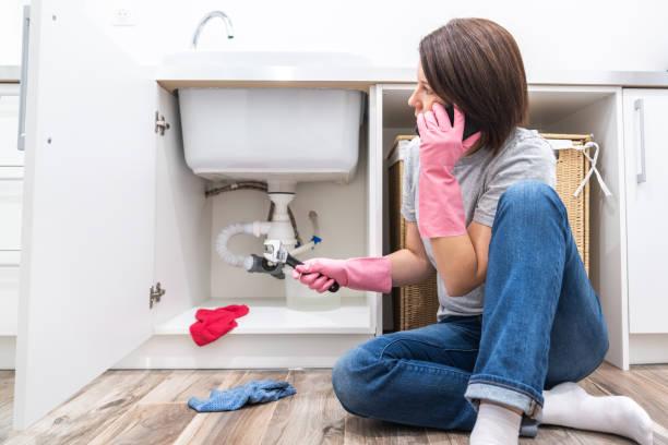 kvinna sitter nära läckande sink åker för hjälp via telefon - water pipes bildbanksfoton och bilder
