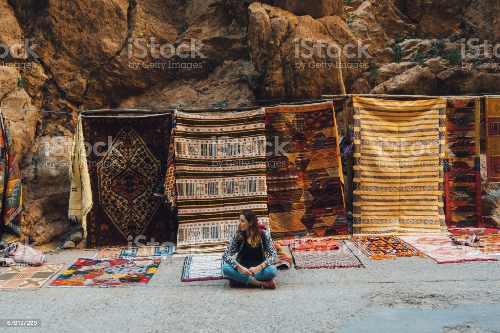 Woman sitting near the carpets in Morocco stock photo