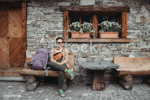 Young Caucasian woman with hiking backpack  sitting near the old house in Swiss Alps