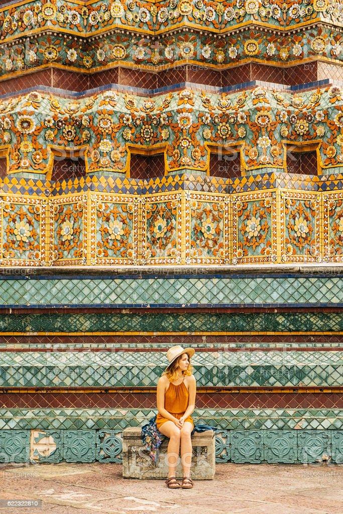 Woman sitting near the stupa in Wat Pho temple stock photo