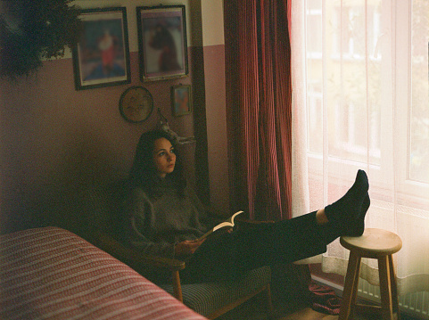 Portrait of woman sitting near the window and reading book