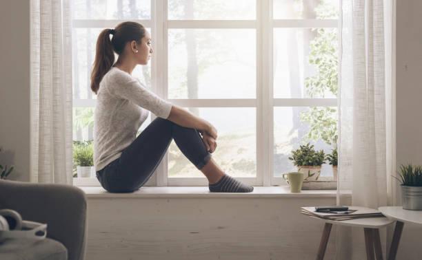 Frau sitzt neben einem Fenster und wegsehen, erwägt sie die Panorama außerhalb – Foto