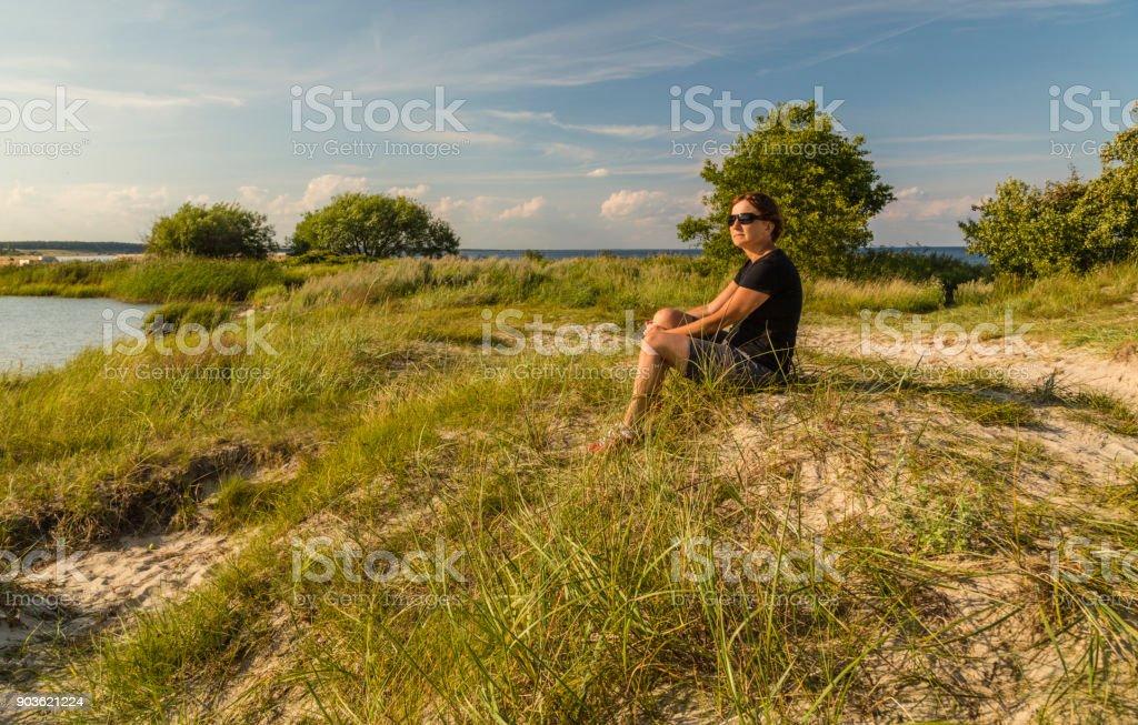 Woman sitting on a beach stock photo