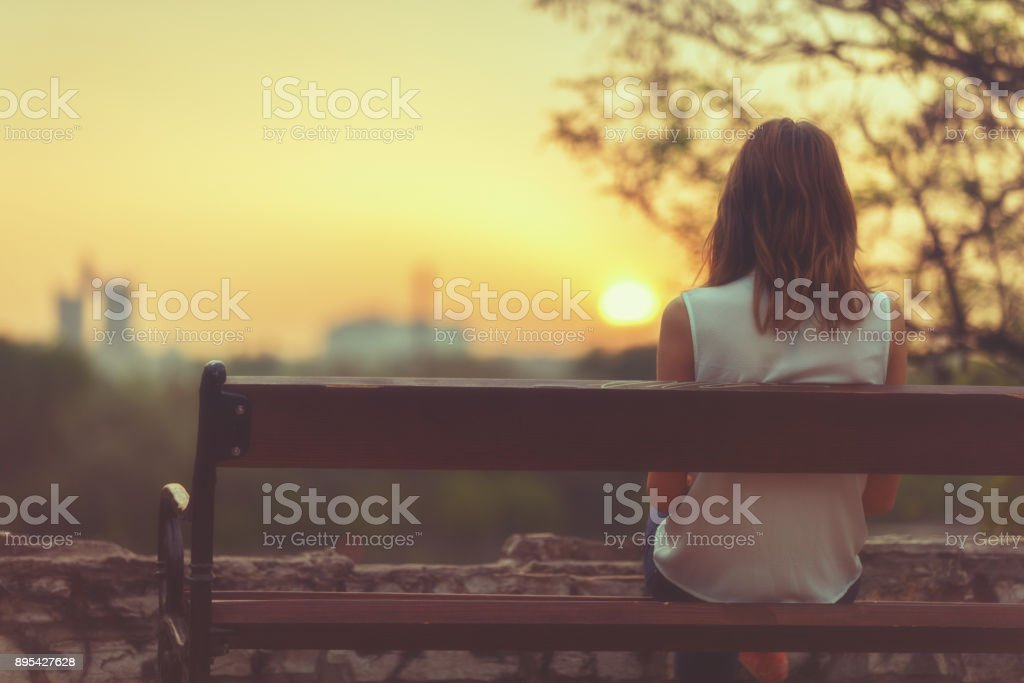 Woman sitting on a bench and watching the distant city scenery. stock photo
