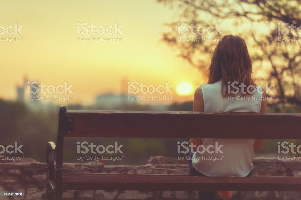 Mulher sentada num banco e observar a paisagem de cidade distante. - foto de acervo