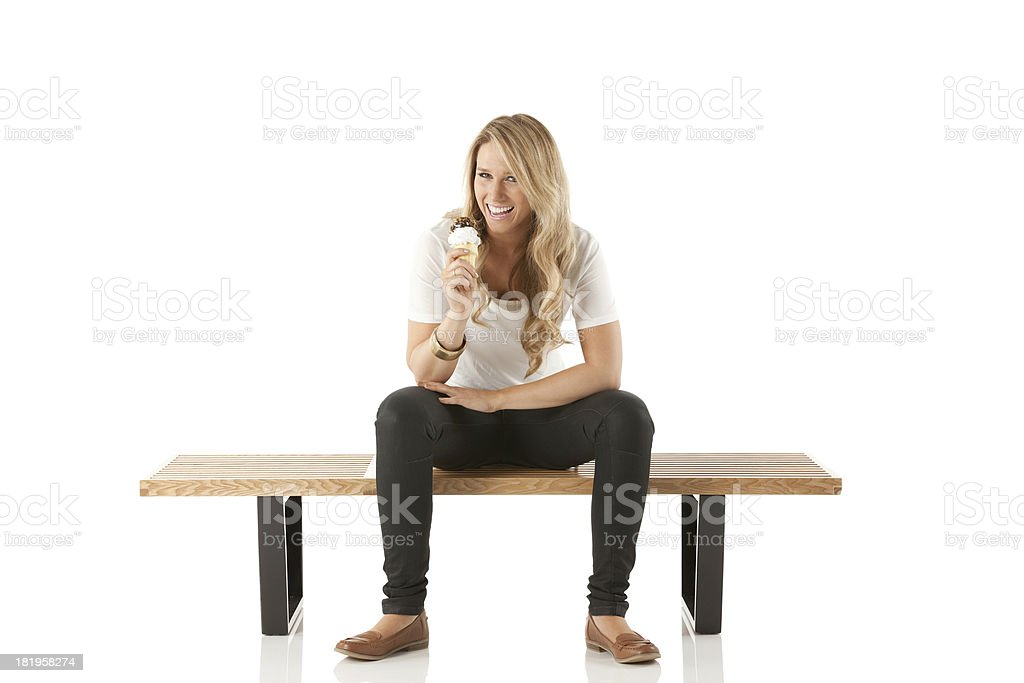 Woman sitting on a bench enjoying ice cream stock photo
