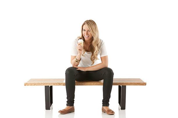 mujer sentada en un banco disfrutar de helado - piernas abiertas mujer fotografías e imágenes de stock
