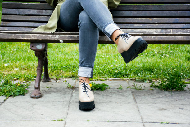 Woman sitting on a bench in a park stock photo