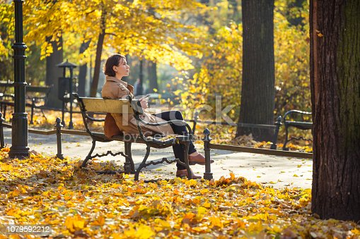 Woman sitting on a bench in an autumnal park in sunny, beautiful day (Kraków, Poland). yellow foliage