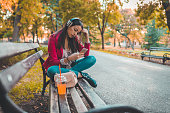 Woman sitting on a bench in the public park and listening to music