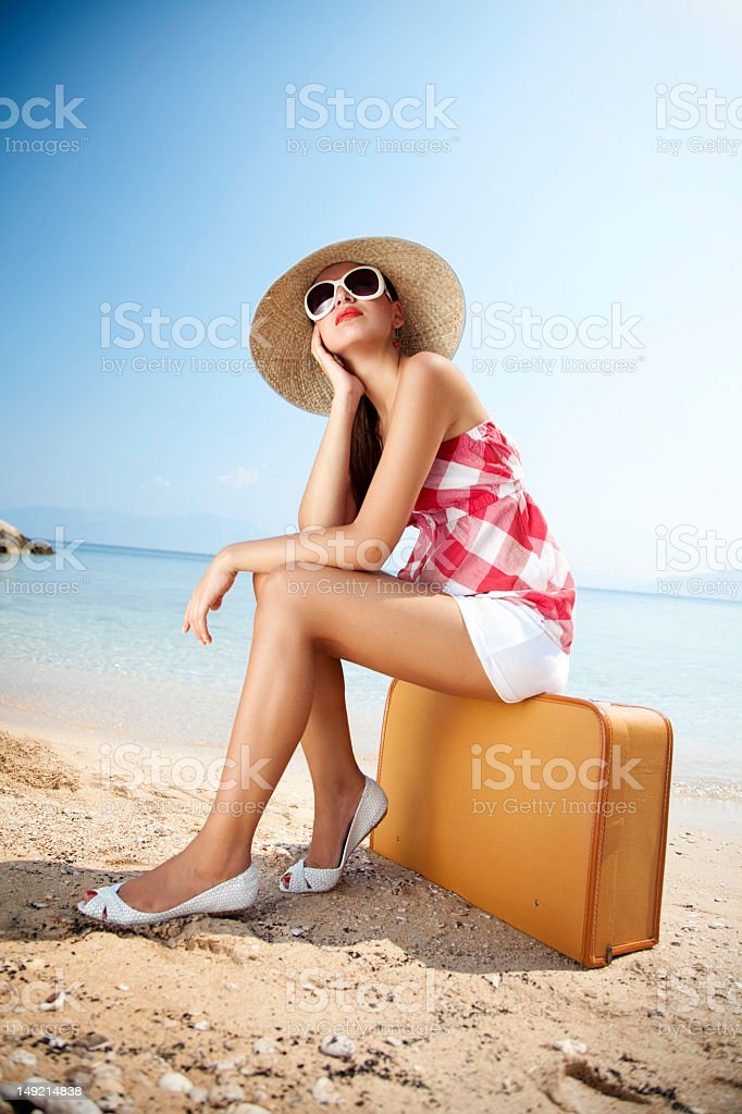 A woman sitting on a briefcase on the beach stock photo