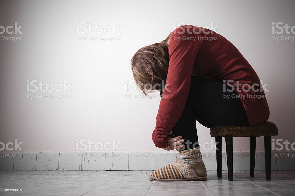 Woman sitting on a chair alone stock photo