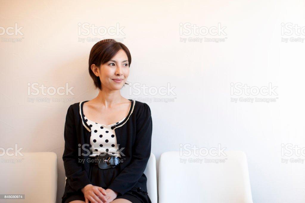 Mulher sentada em uma cadeira, olhando para fora - foto de acervo