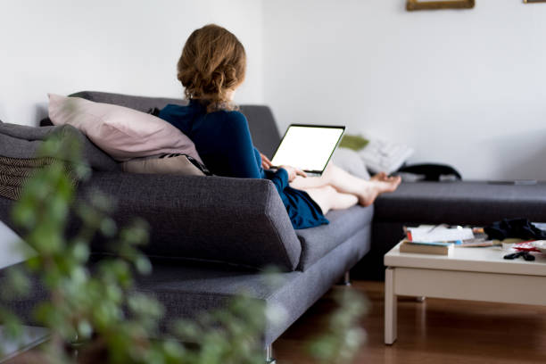 Woman sitting on a couch at home and is working on laptop with blank screen from home stock photo