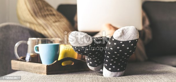 Woman sitting on a couch in the living room with warm socks in a winter morning. Girl using laptop and works at home, having natural breakfast with tea coffee and fruits. Focus on feet in foreground