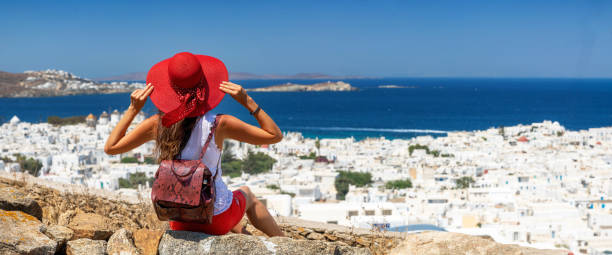Woman sitting on a hill over the white town of Mykonos island stock photo